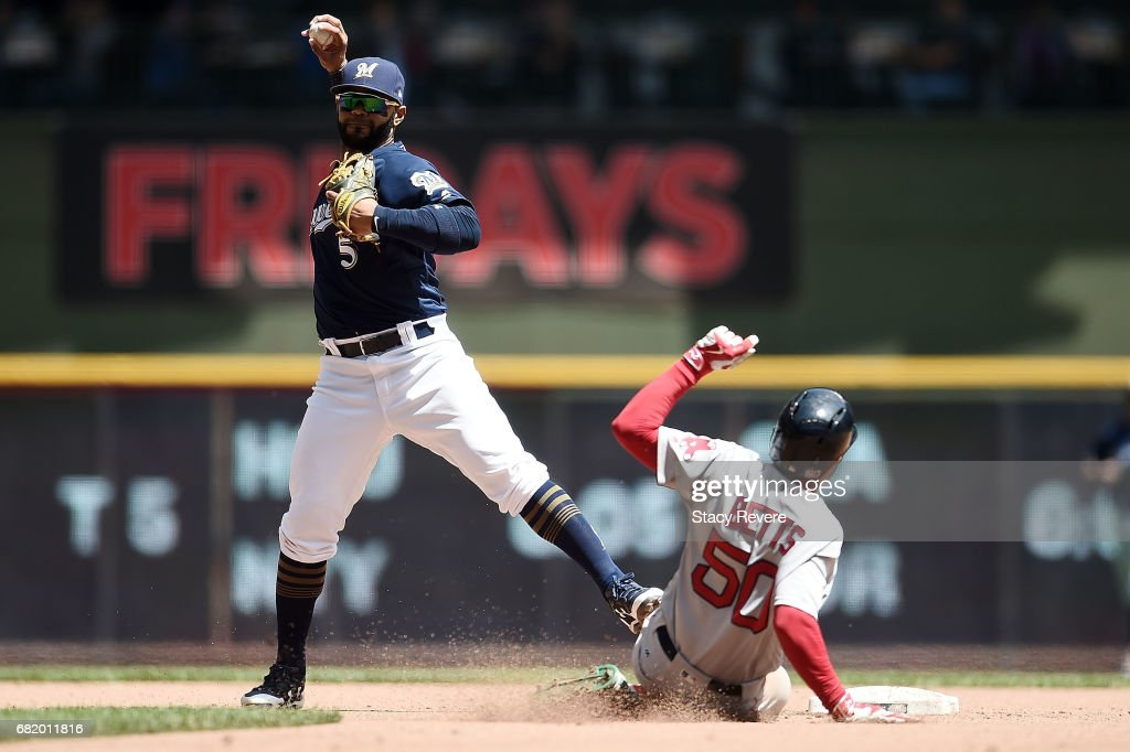 Mookie Betts #50 of the Boston Red Sox is forced out at second base as Jonathan Villar #5 of the Milwaukee Brewers makes a throw to first base during the fifth inning of a game at Miller Park on May 11, 2017 in Milwaukee, Wisconsin.