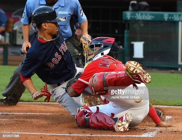 Mookie Betts of the Boston Red Sox is safe at home scoring the first run of the game as the ball pops out of the glove of Martin Maldonado of the Los...