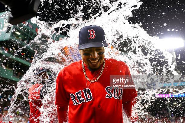 Mookie Betts of the Boston Red Sox is showered in Gatorade after the Boston Red Sox defeated the New York Yankees 105 at Fenway Park on July 26 2019...