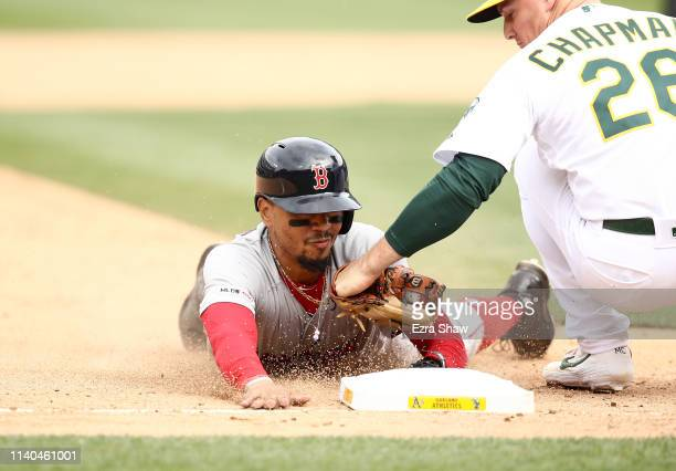 Mookie Betts of the Boston Red Sox is tagged out by Matt Chapman of the Oakland Athletics at third base in the ninth inning at OaklandAlameda County...