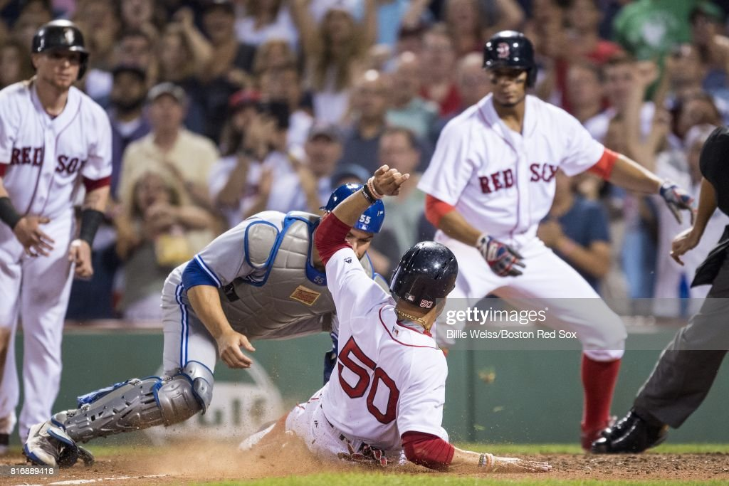 Mookie Betts #50 of the Boston Red Sox is tagged out by Russell Martin #55 of the Toronto Blue Jays while attempting to score during the seventh inning of a game on July 17, 2017 at Fenway Park in Boston, Massachusetts.