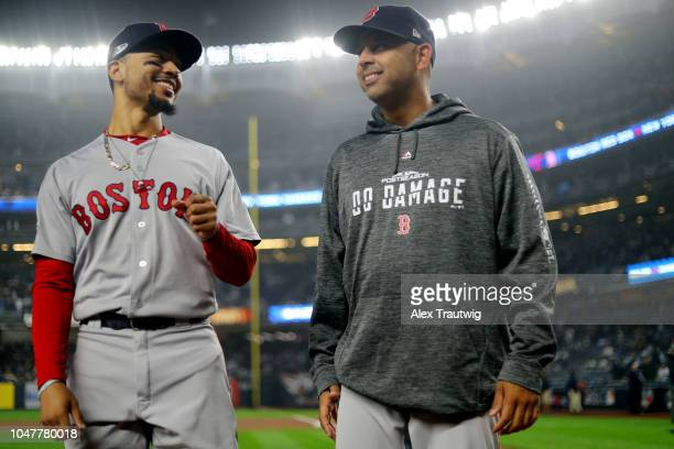 Mookie Betts of the Boston Red Sox jokes with manager Alex Cora during player introductions prior to Game 3 of the ALDS against the New York Yankees...