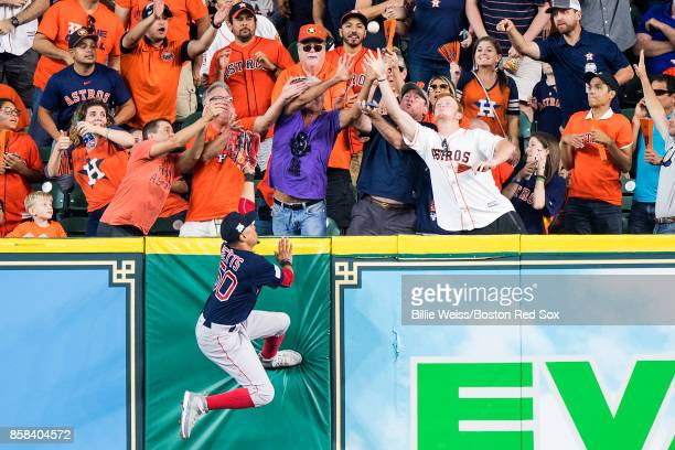 Mookie Betts of the Boston Red Sox leaps as he attempts to catch a solo home run hit by George Springer of the Houston Astros during the third inning...