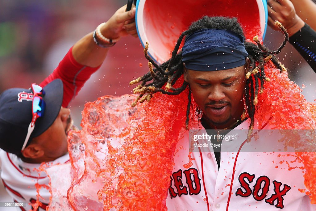 Mookie Betts #50 of the Boston Red Sox, left, and Eduardo Rodriguez #52 (not pictured) dump red Powerade on Hanley Ramirez #13 of the Boston Red Sox after defeating the Tampa Bay Rays 8-6 at Fenway Park on August 31, 2016 in Boston, Massachusetts.