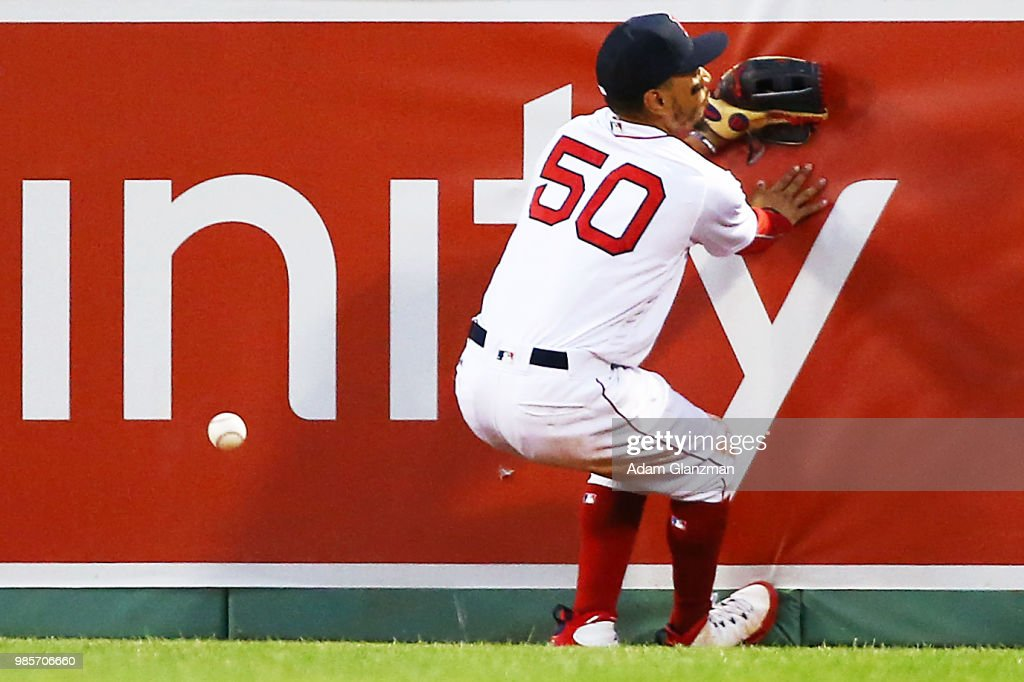 Mookie Betts #50 of the Boston Red Sox misplays a ball off of the right outfield wall in the third inning of a game against the Los Angeles Angels at Fenway Park on June 27, 2018 in Boston, Massachusetts.