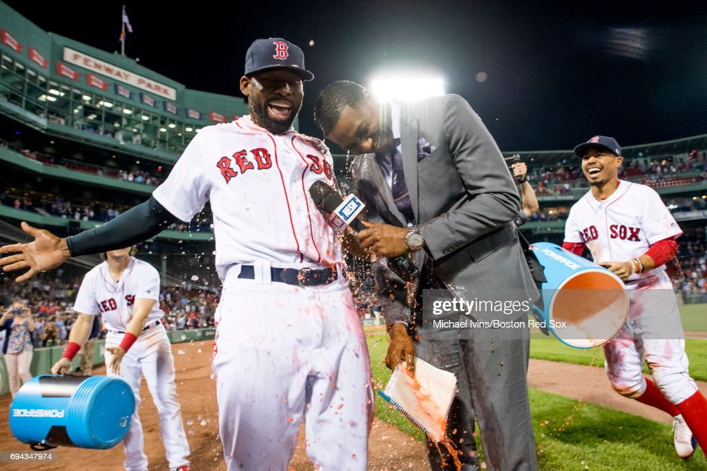 Mookie Betts #50 of the Boston Red Sox reacts after dousing NESN reporter Jahmai Webster and Jackie Bradley Jr. #19 after Bradley's two-run home run in the ninth inning led to a 5-3 win over the Detroit Tigers at Fenway Park on June 9, 2017 in Boston, Massachusetts.