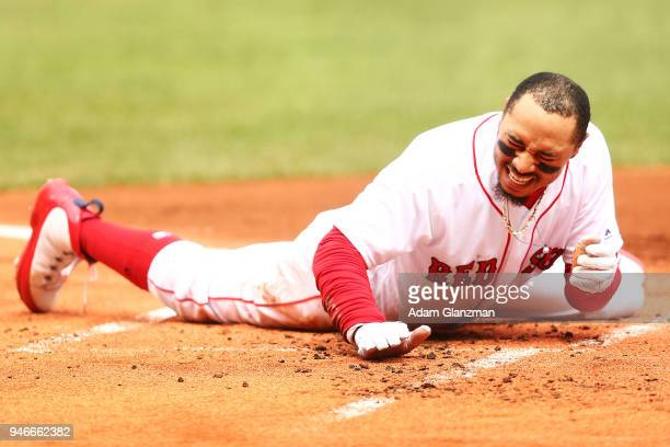 Mookie Betts of the Boston Red Sox reacts after sliding safely into home plate after the ball got away from Chance Sisco of the Baltimore Orioles in...