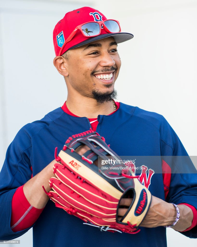 Mookie Betts #50 of the Boston Red Sox reacts as he holds a Wilson glove during a team workout on February 21, 2018 at jetBlue Park at Fenway South in Fort Myers, Florida .