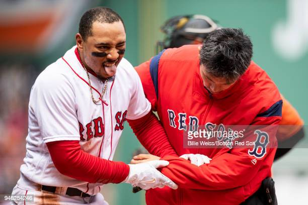 Mookie Betts of the Boston Red Sox reacts as he is tended to by trainer Masai Takahashi during the first inning of a game against the Baltimore...