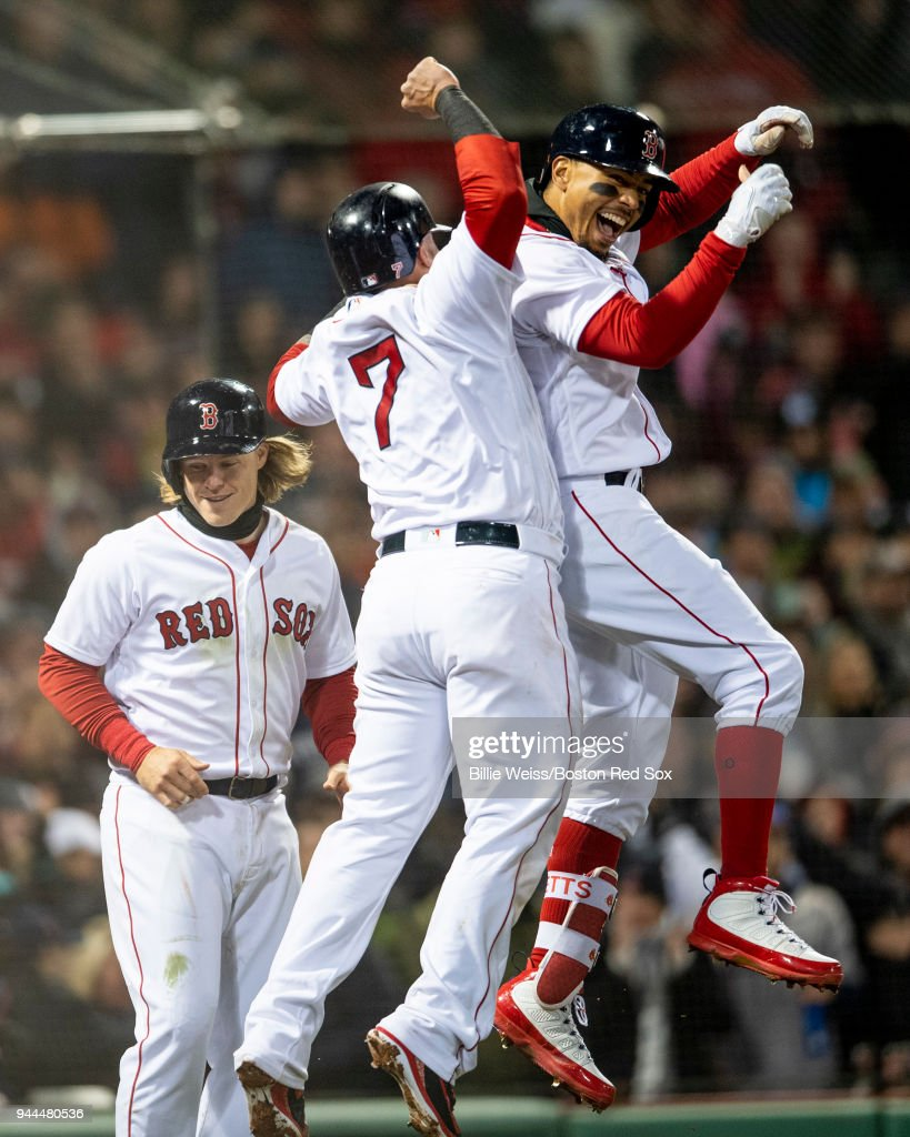 Mookie Betts #50 of the Boston Red Sox reacts with Christian Vazquez #7 and Brock Holt #12 after hitting a grand slam home run during the sixth inning of a game against the New York Yankees on April 10, 2018 at Fenway Park in Boston, Massachusetts.