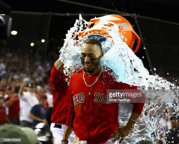 Mookie Betts of the Boston Red Sox recieves a Gatorade bath from JD Martinez of the Boston Red Sox after hitting a walk off home in the bottom of the...