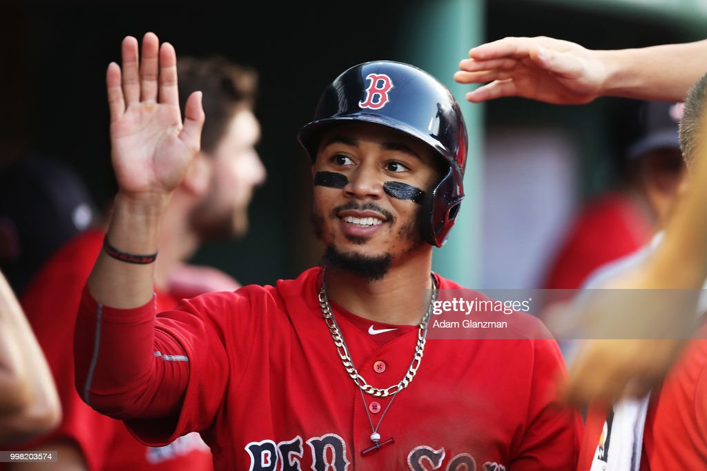 Mookie Betts #50 of the Boston Red Sox returns to the dugout after scoring in the second inning of a game against the Toronto Blue Jays at Fenway Park on July 13, 2018 in Boston, Massachusetts.