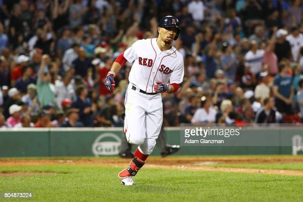 Mookie Betts of the Boston Red Sox rounds the bases after hitting a solo home run in the fourth inning of a game against the Minnesota Twins at...
