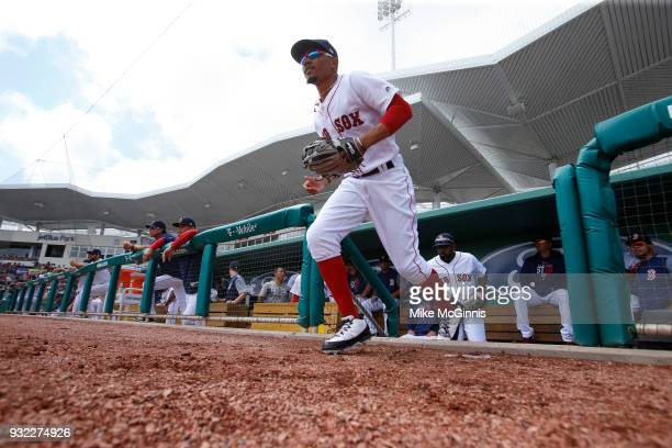 Mookie Betts of the Boston Red Sox runs onto the field during the Spring Training game against the Baltimore Orioles at Jet Blue Park on March 11...
