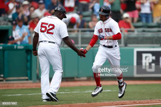 Mookie Betts of the Boston Red Sox runs the bases after hitting a solo home run during the first inning of the Spring Training game against the...