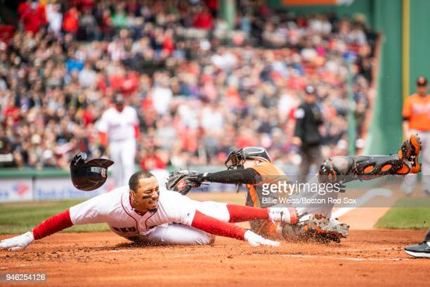 Mookie Betts of the Boston Red Sox slides as he evades the tag of Chance Sisco of the Baltimore Orioles to score during the first inning of a game...