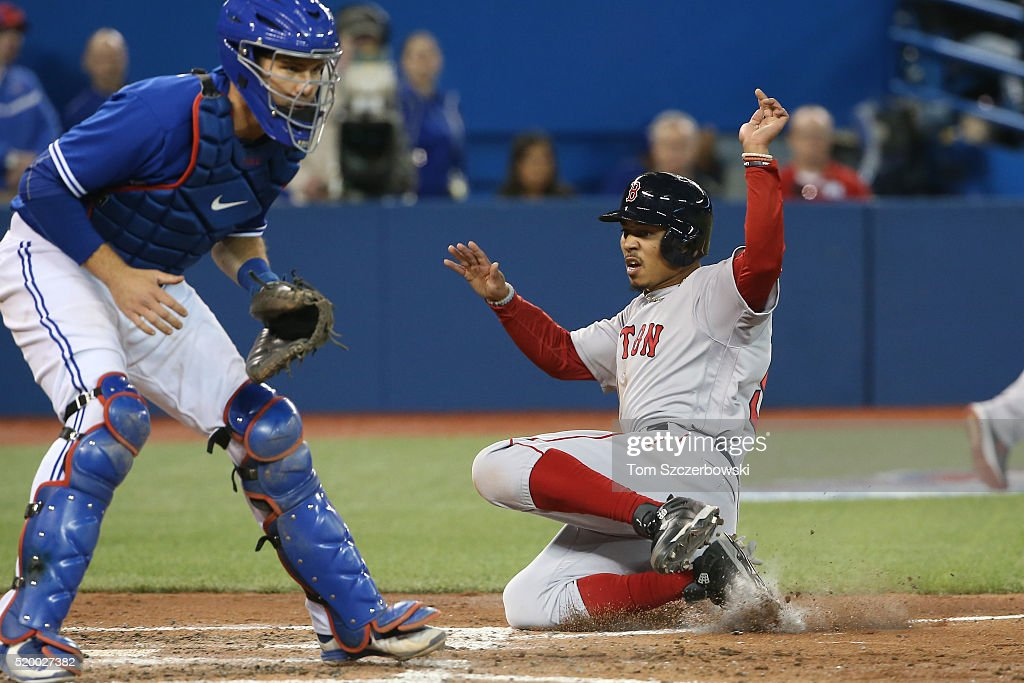 Mookie Betts #50 of the Boston Red Sox slides home safely to score a run in the sixth inning during MLB game action as Josh Thole #22 of the Toronto Blue Jays waits for the throw on April 9, 2016 at Rogers Centre in Toronto, Ontario, Canada.