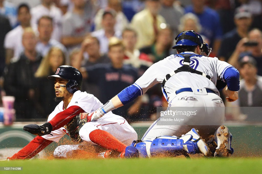 Mookie Betts #50 of the Boston Red Sox slides into home past Danny Jansen #9 of the Toronto Blue Jays to score a run during the eighth inning at Fenway Park on September 11, 2018 in Boston, Massachusetts.