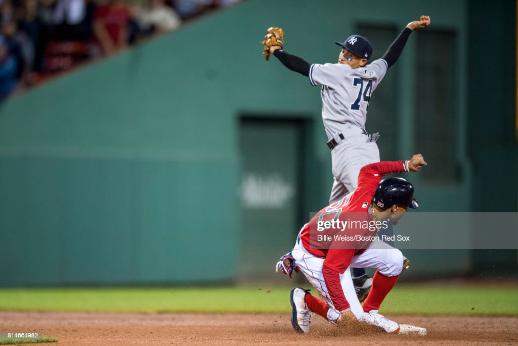 Mookie Betts #50 of the Boston Red Sox slides into second as Ronald Torreyes #74 of the New York Yankees leaps for an overthrown ball during the ninth inning of a game on July 14, 2017 at Fenway Park in Boston, Massachusetts.