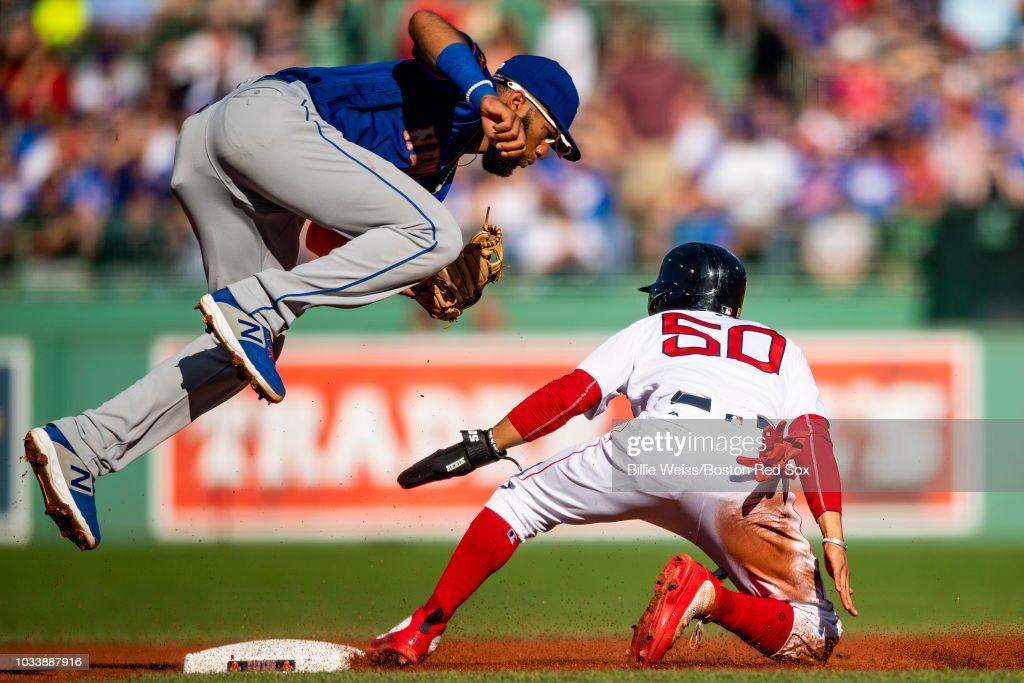 Mookie Betts #50 of the Boston Red Sox slides into second base as Amed Rosario #1 of the New York Mets jumps to attempt to catch an overthrown ball during the first inning of a game against the New York Mets on September 15, 2018 at Fenway Park in Boston, Massachusetts.