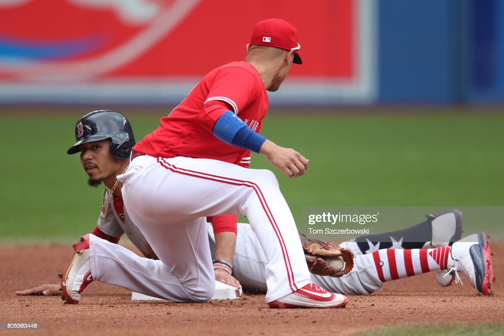 Mookie Betts #50 of the Boston Red Sox slides into second base with a stolen base in the fifth inning during MLB game action as Ryan Goins #17 of the Toronto Blue Jays applies the tag at Rogers Centre on July 1, 2017 in Toronto, Canada.