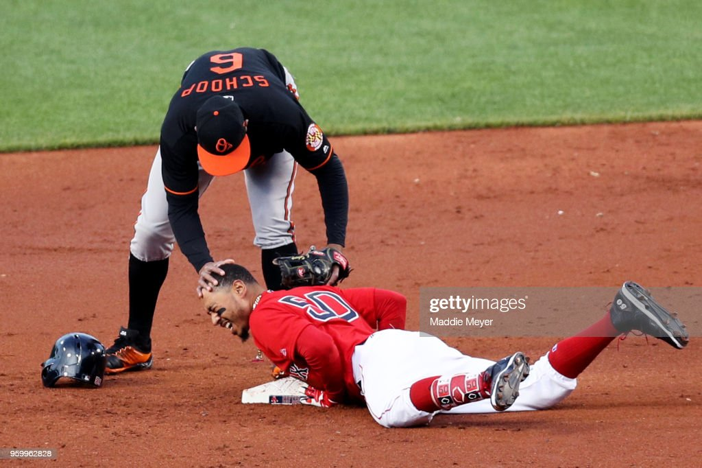 Mookie Betts #50 of the Boston Red Sox slides into second past Jonathan Schoop #6 of the Baltimore Orioles after hitting a double in the first inning at Fenway Park on May 18, 2018 in Boston, Massachusetts.