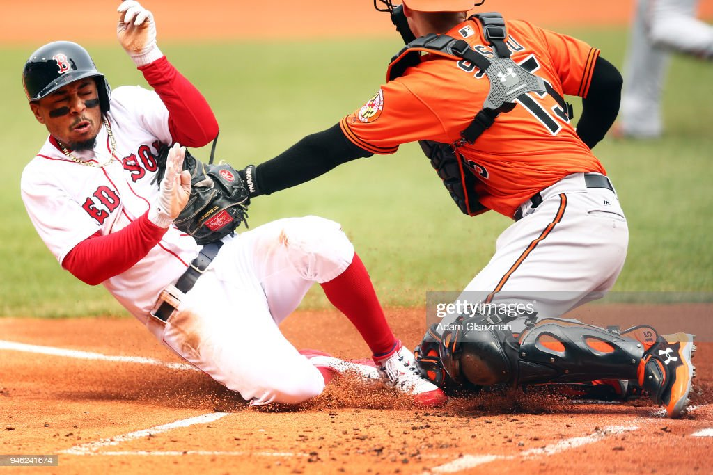 Mookie Betts #50 of the Boston Red Sox slides safely into home plate as the ball gets away from Chance Sisco #15 of the Baltimore Orioles in the first inning of a game at Fenway Park on April 14, 2018 in Boston, Massachusetts.