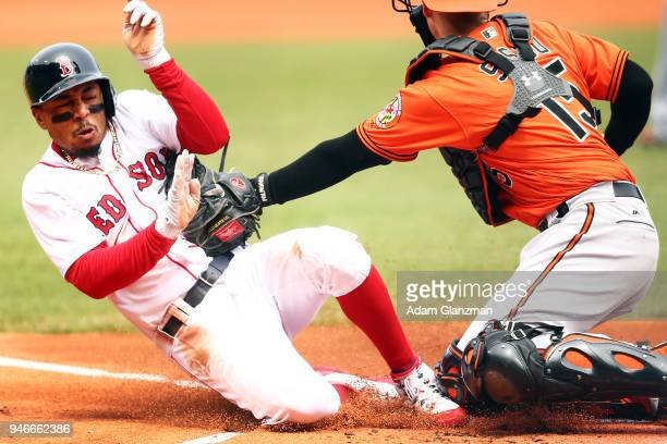 Mookie Betts of the Boston Red Sox slides safely into home plate as the ball gets away from Chance Sisco of the Baltimore Orioles in the first inning...