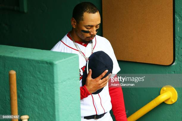 Mookie Betts of the Boston Red Sox stands for the national anthem before a game against the Baltimore Orioles at Fenway Park on April 14 2018 in...