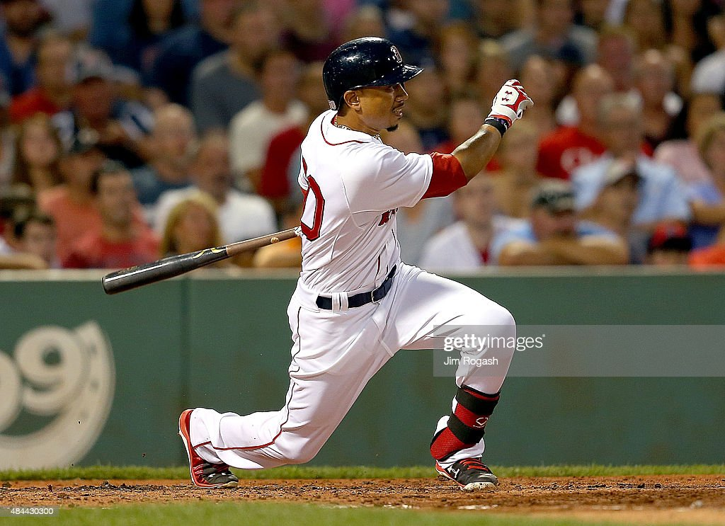 Mookie Betts #50 of the Boston Red Sox starts his swing as he double in three runs in the second inning against the Cleveland Indians at Fenway Park on August 18, 2015 in Boston, Massachusetts.