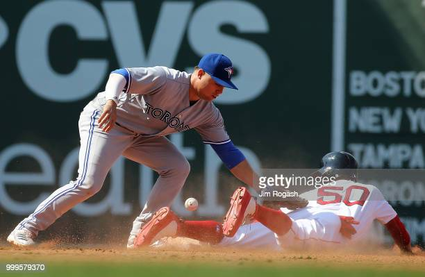 Mookie Betts of the Boston Red Sox steal second base as Aledmys Diaz of the Toronto Blue Jays has trouble handling the throw in the seventh inning at...