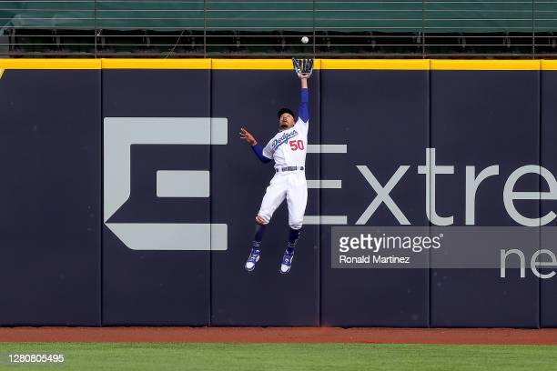 Mookie Betts of the Los Angeles Dodgers catches a fly ball at the wall on a hit by Marcell Ozuna of the Atlanta Braves during the fifth inning in...