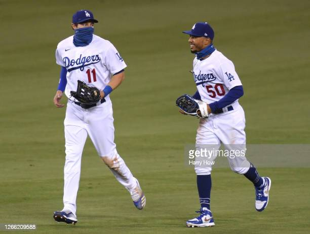 Mookie Betts of the Los Angeles Dodgers celebrates a three homerun night and an 11-2 win over the San Diego Padres with A.J. Pollock at Dodger...
