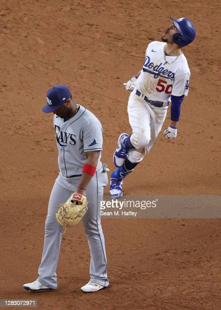 Mookie Betts of the Los Angeles Dodgers celebrates as he rounds the bases after hitting a solo home run as Yandy Diaz of the Tampa Bay Rays looks on...