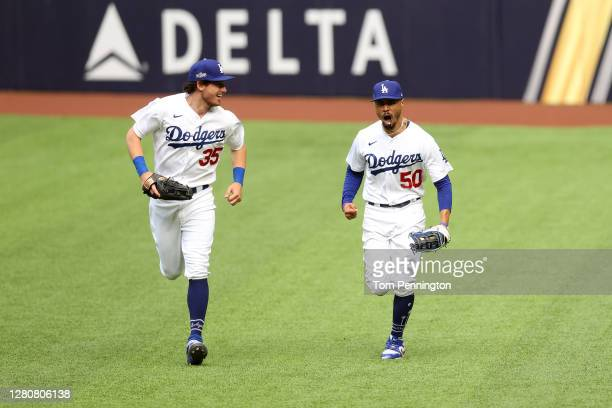 Mookie Betts of the Los Angeles Dodgers celebrates with Cody Bellinger after catching a fly ball at the wall on a hit by Marcell Ozuna of the Atlanta...