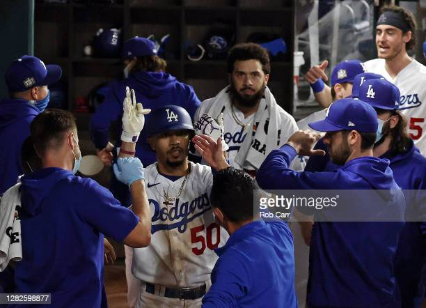 Mookie Betts of the Los Angeles Dodgers celebrates with his teammates after hitting a solo home run against the Tampa Bay Rays during the eighth...