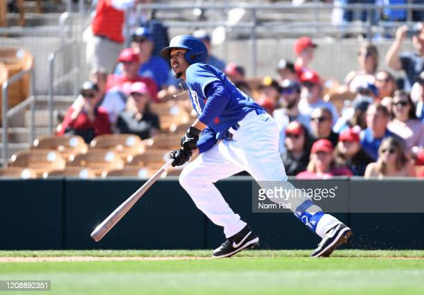 Mookie Betts of the Los Angeles Dodgers hits a fly ball out to left field of a spring training game against the Los Angeles Angels at Camelback Ranch...