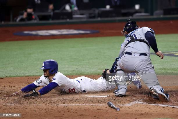 Mookie Betts of the Los Angeles Dodgers slides in safely past Mike Zunino of the Tampa Bay Rays to score a run on a fielders choice hit by Corey...