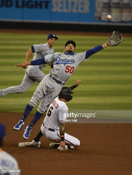 Mookie Betts of the Los Angeles Dodgers tries to make a leaping catch on a high throw to second base by teammate Austin Barnes as David Peralta of...