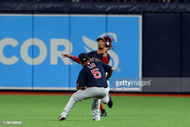 Mookie Betts of the Red hustles in to make the catch just behind infielder TzuWei Lin during the MLB regular season game between the Boston Red Sox...