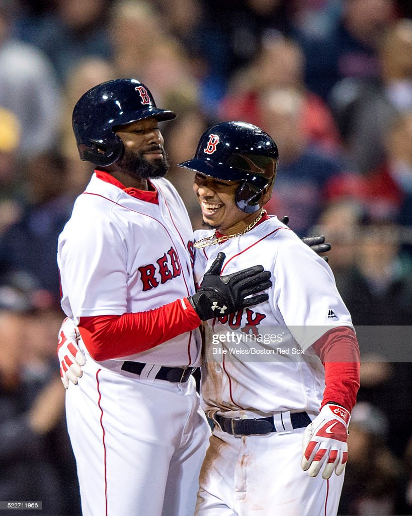 Mookie Betts #50 reacts with Jackie Bradley Jr. #25 of the Boston Red Sox after hitting a two run home run during the second inning of a game against the Tampa Bay Rays on April 20, 2016 at Fenway Park in Boston, Massachusetts .