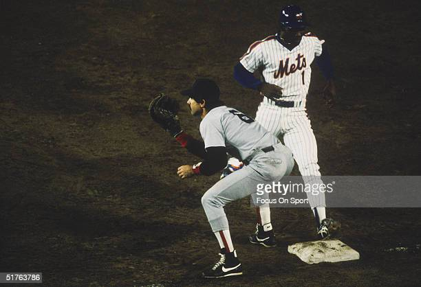 Mookie Wilson of the New York Mets gets back to the bag while Bill Buckner of the Boston Red Sox waits for the pickoff throw during the World Series...