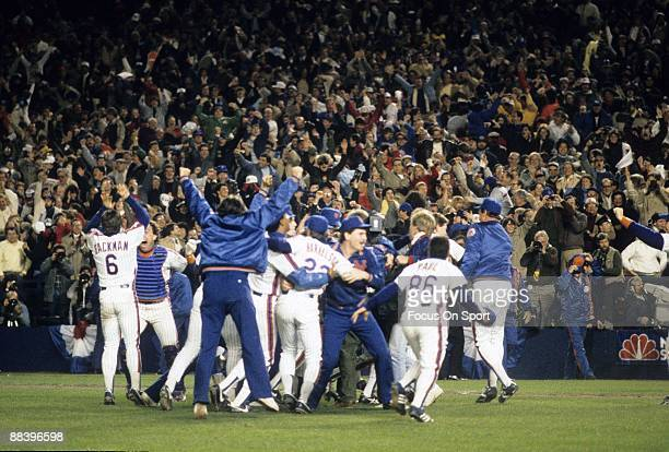 Mookie Wilson of the New York Mets is mobbed by teammates with jubilation after he hit the ground ball that scored teammate Ray Knight the winning...