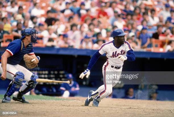 Mookie Wilson of the New York Mets watches the flight of the ball as he runs to first base during a 1984 season game against the Chicago Cubs at Shea...