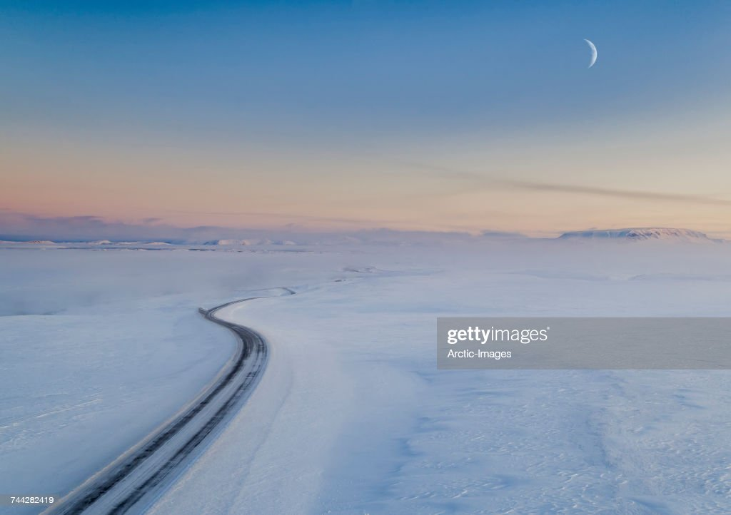 Moon and snowy mountain road. Myvatnsoraefi mountain pass in the winter, Myvatn, Northern Iceland. This image is shot with a drone. : Stock Photo