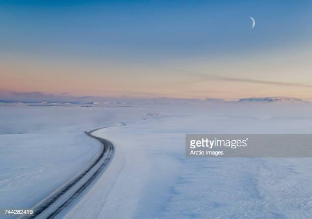 Moon and snowy mountain road. Myvatnsoraefi mountain pass in the winter, Myvatn, Northern Iceland. This image is shot with a drone.