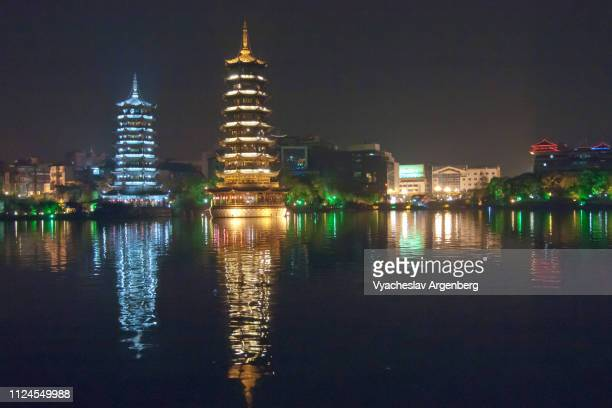 moon and sun pagodas on guilin lake, beautifully illuminated at night, china - argenberg imagens e fotografias de stock
