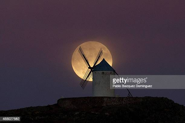 A moon appears behind a windmill a day before the supermoon is full on September 8 2014 in Consuegra in Toledo province Spain Consuegra belongs to a...