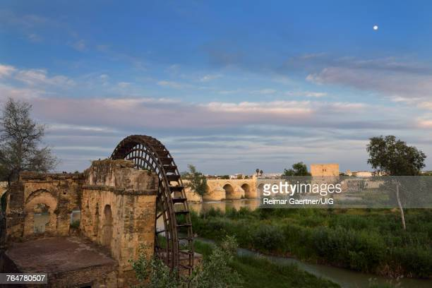 Moon at sundown over Guadalquivir River with Albolafia Waterwheel Roman Bridge and Calahorra Tower Cordoba