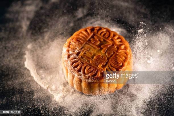 moon cake with flour taken with high speed sync. - moon cake stock pictures, royalty-free photos & images